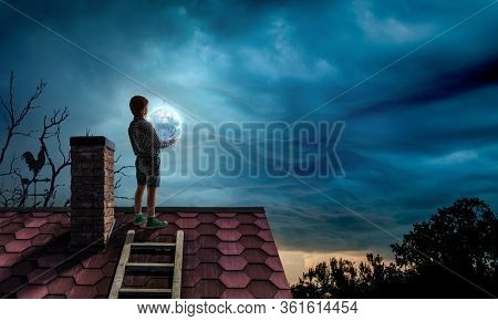 Boy holding moon at night on roof top