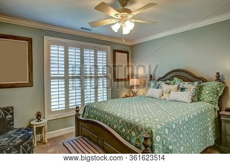 Quaint comfortable guest bedroom with bed and windows.