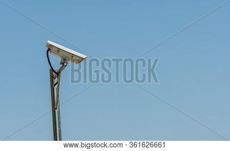 Cctv Camera On Shinny Chrome Plated Pole Against Clear Blue Sky.