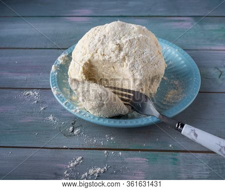 Curd Dough For Lazy Dumplings In A Ceramic Blue Plate And A Tablespoon Stand On A Wooden Table