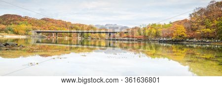 Tranquil Autumn Scene Scotland. Colourful Trees And Bridge Reflected In Calm Water. Peacefulness.