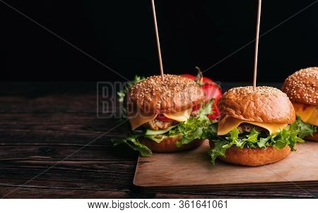 Three Homemade Hamburgers With Meat, Cheese, Lettuce And Tomatoes