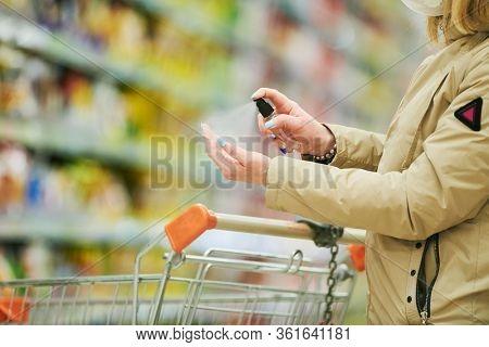 woman uses antibacterial sanitizer sprayer while shopping at food supermarket at coronavirus covid-19 outbreak