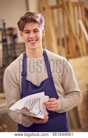 Portrait Of Male Student Studying For Carpentry Apprenticeship At College With Plans For Staircase