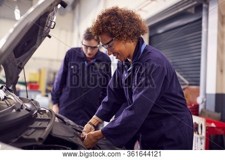 Female Tutor With Students Looking At Car Engine On Auto Mechanic Apprenticeship Course At College