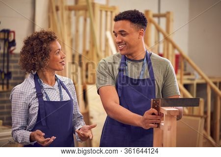 Tutor With Male Carpentry Student In Workshop Studying For College Apprenticeship Using Set Square