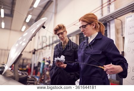 Male And Female Students Checking Car Oil Level On Auto Mechanic Apprenticeship Course At College