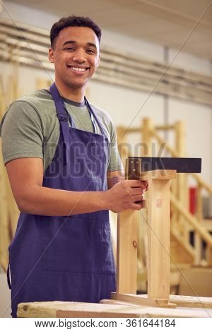 Portrait Of Male Student Studying For Carpentry Apprenticeship At College Using Set Square