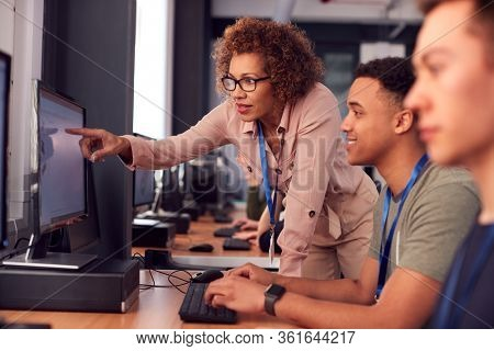 Group Of College Students With Tutor Studying Computer Design Sitting At Monitors In Classroom