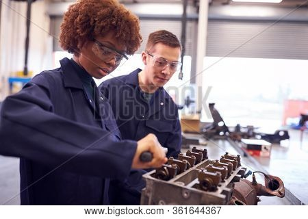 Male And Female Students Work On Car Engine Block On Auto Mechanic Apprenticeship Course At College
