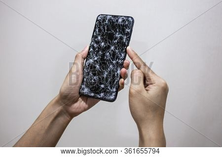 Woman Hands Holding Smartphone With Broken Or Cracked Screen On White Background. Not Open And Avail