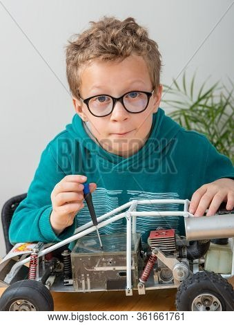 A Little Boy Repairing A Model Radio-controlled Car At Home