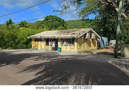 Mahe, Seychelles - July 7, 2011: A Local Woman Going In Small Shop On A Street On Seychelles Islands