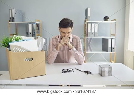 Unemployment. Dismissal. Dismissed Businessman Is Upset With A Cardboard Box Holding His Head In His