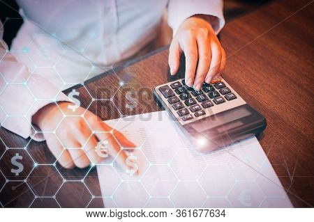 Female Accountant Sitting At Table In Office And Working With Financial Document And Calculator. Bus