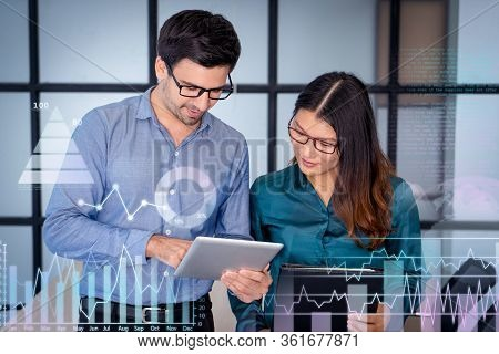 Caucasian Supervisor Helping New Asian Employee. Office Workers Using Tablet With Virtual Analysis C