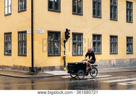 Stockholm, Sweden - August 8, 2019: Hipster Man Riding An Old Bicycle In Sofo Area A Rainy Day. It I