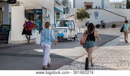 Tuk Tuk Carrying Tourists Traveling On A Street Albufeira, Portugal