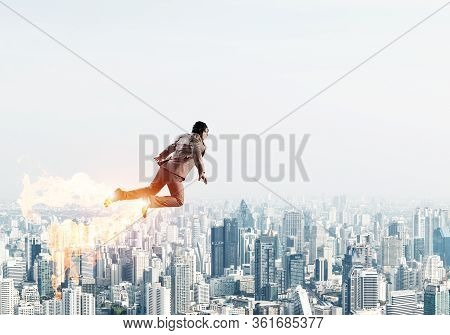 Businessman In Suit And Aviator Hat Flying In Blue Sky As Superhero. Business Person As Superman Lau