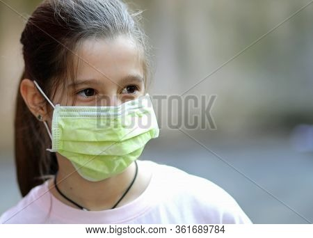 Pretty Little Girl With Green Surgical Mask During Lock Down Caused By Corona Virus