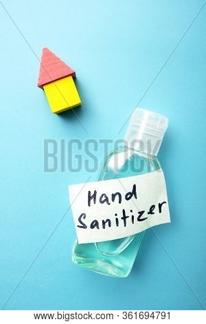 A Bottle Of Hand Sterilizer And A Little Yellow And Pink House On Blue Background. Hand Cleaning And