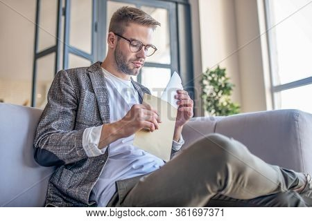 Stylish Fair-haired Man In Eyeglasses Opening The Envelope