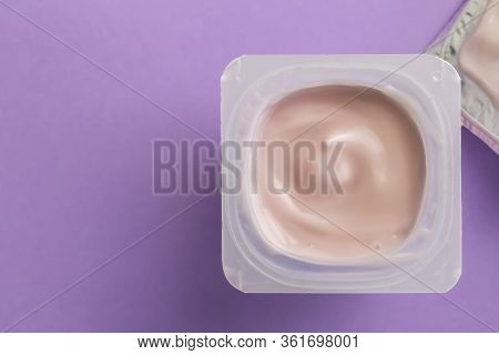 Yogurt Cup With Strawberry Yoghurt Isolated On Lilac Background With Space For Text
