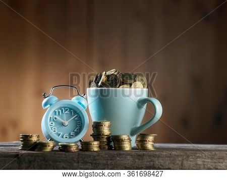 alarm clock and mug filled up with coins -time is money
