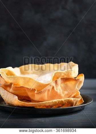 Indian Snacks. Close Up Of Rustic Indian Papadum Crisp On A Dark Background With Copy Space. Selecti