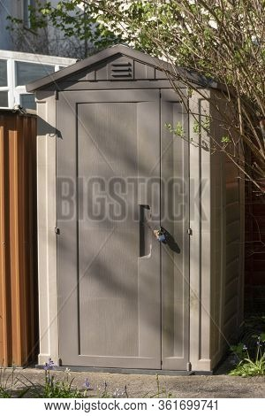 A Close Up View Of A Outside Plastic Shed Or Storage Unit That Has A Small Lock On It Out In The Sma
