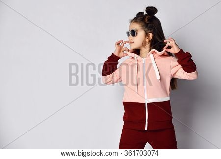 Frolic Curious Kid Girl In Modern Fashion Two-colored Pink Brown Sportsuit And Sunglasses Stands Hol