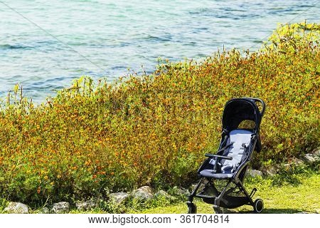 A Baby Carriage, A Cradle For Newborns Of Brown Color With A Bag For A Carriage On The Background Of