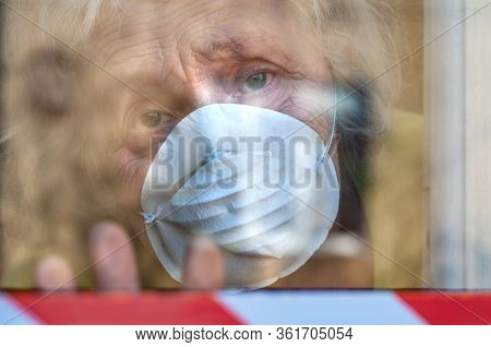 A Sad Elderly Wrinkled Woman Is Looking Through The Window In The Respiratory Mask Of Her House. Sel