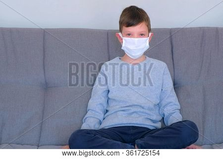Child Boy Is Putting On Medical Protective Mask On Face, Coronavirus Quarantine Pandemic. He Is Sitt