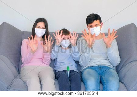 Family Mom, Son And Dad In Protective Medical Masks Disinfect Hands Alcohol Spray At Home Quarantine