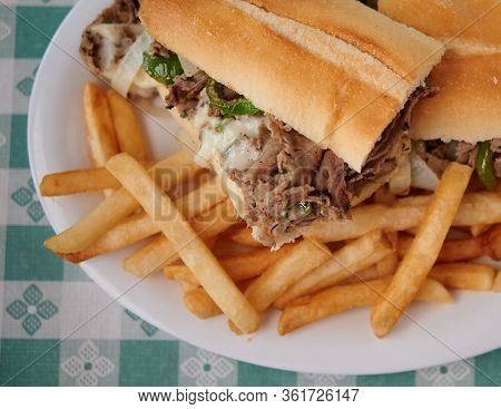 Steak Sandwich With Green Peppers And Melted Cheese On The Plate With French Fries