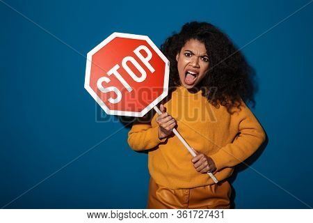Image of displeased screaming young african woman posing isolated over blue wall background holding stop sign.