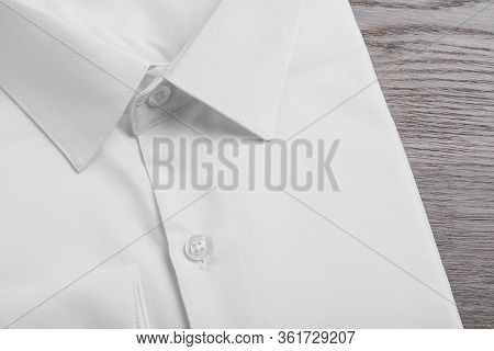 Stylish White Shirt On Wooden Table, Closeup. Dry-cleaning Service