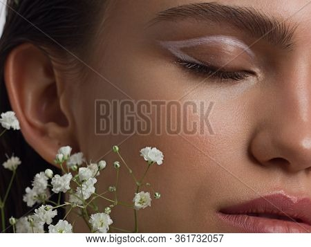 Close Up Half Portrait Of A Face With Beautiful Skin And Nude Makeup, Eyeliner And Long Eyelashes, P