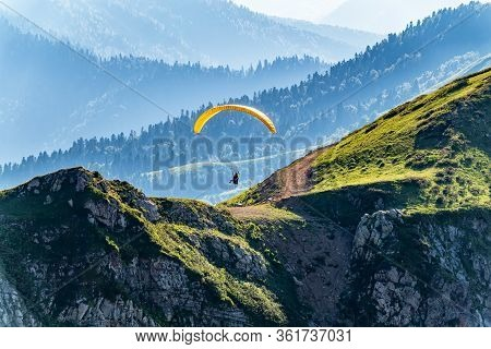 Yellow Paraglider Over The Green Mountain Slope. Paraglider Fly Over Mountain Slope On Sunny Summer