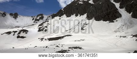 High Sunlit Mountains With Snow Cornice And Avalanche Track, Snowy Plateau And Two Small Silhouettes