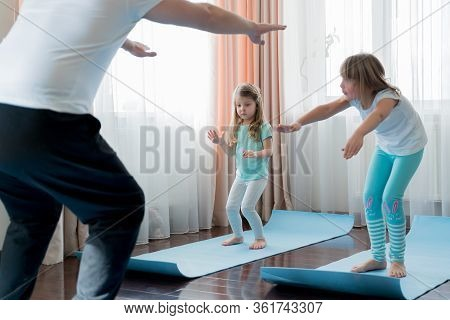 Home Workout In Flat.dad Teaching Little Girls Fitness, Daughters. Physical Morning Exercises On Blu