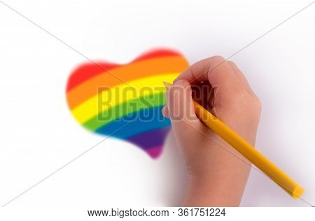 The Concept Of The Pursuit Of The Rainbow. A Hand With A Pencil Draws A Heart In Rainbow Colors