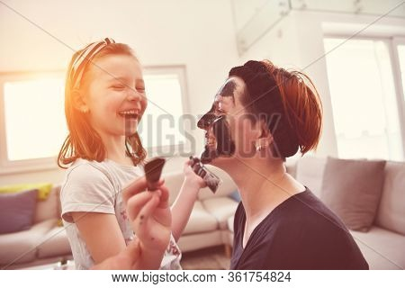 Family at home beauty treatment during coronavirus pandemic stay at home quarantine. Mother and little girl daughter  make a facial mask.