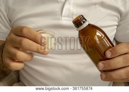 Man In White T-shirt Is Pouring Medical Syrup In A Measuring Cup. Young Man Holds Bottle Of Syrup Wi