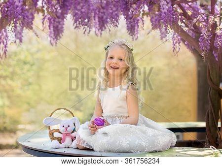 Little girl in wisteria blossom. Easter background