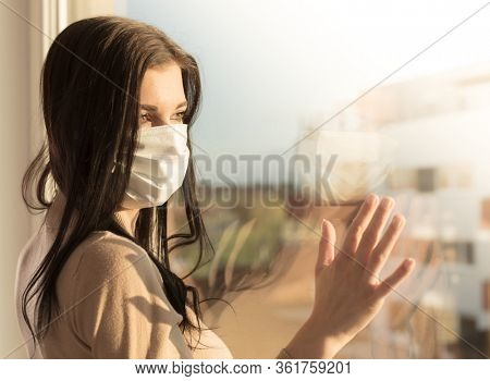 Young woman with veil looking at window, home isolation concept. Covid-19 pandemic situation in self isolation at home. New corona virus changes normal lives.
