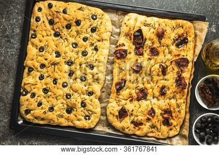 Homemade Italian Focaccia. Traditional Italian pastries with black olives and dried tomatoes. Top view.