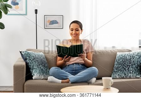 people and leisure concept - happy african american woman sitting on sofa and reading book at home