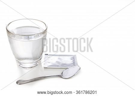Ors Or Oral Rehydration Salt With Glass Of Water, Sachet And Spoon With White Background